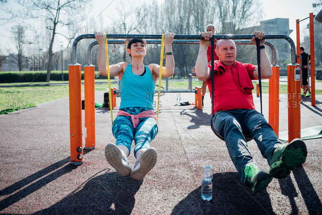 Calisthenics class at outdoor gym, mature man and young woman exercising on parallel bars