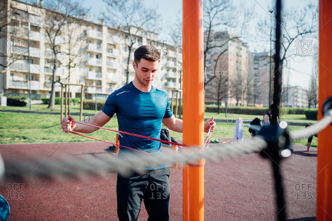 Calisthenics at outdoor gym, young man stretching arms on exercise equipment