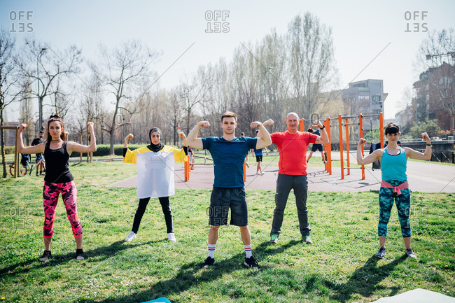 Calisthenics class at outdoor gym, women and men flexing their arm muscles
