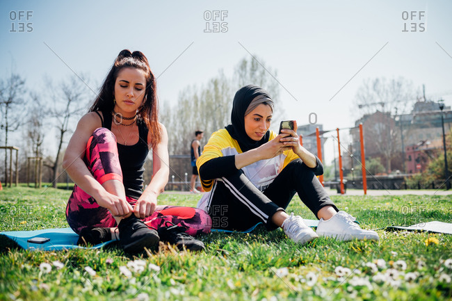 Calisthenics class at outdoor gym, young women sitting on grass tying laces and looking at smartphone