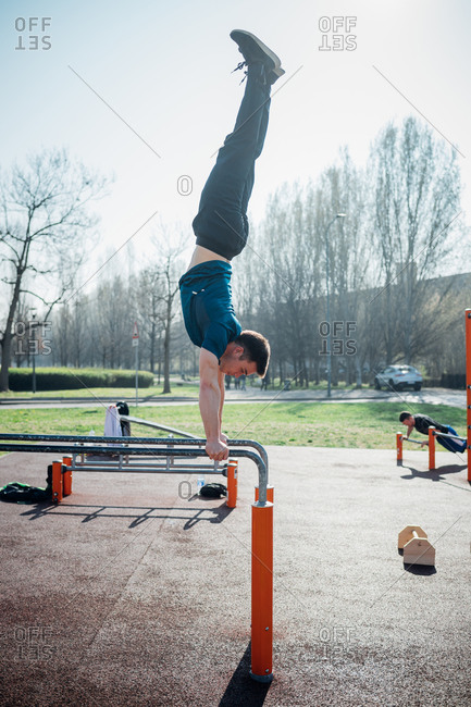Calisthenics at outdoor gym, young man doing handstand on parallel bars