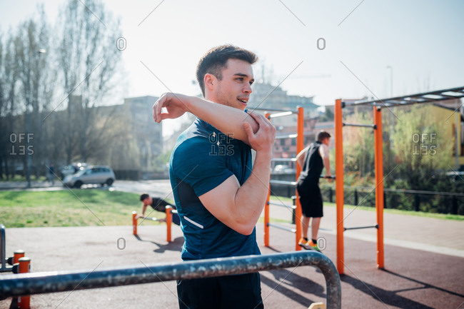 Calisthenics at outdoor gym, young man stretching arm