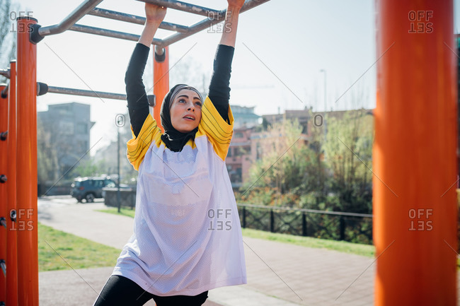 Calisthenics class at outdoor gym, young woman hanging from exercise equipment
