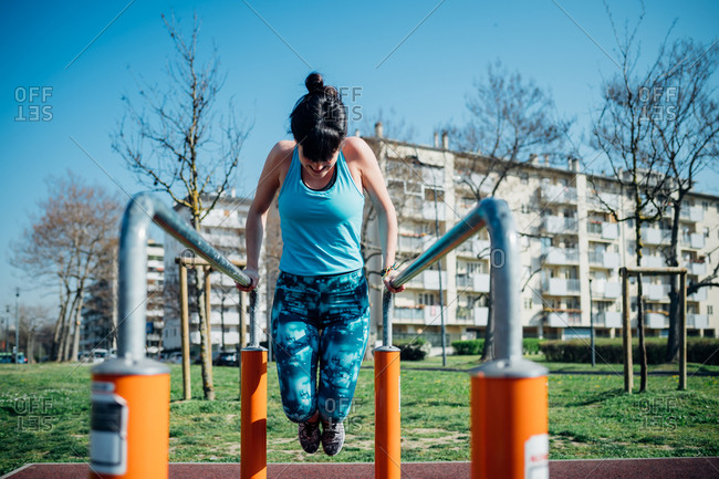 Calisthenics class at outdoor gym, young woman doing push ups on parallel bars