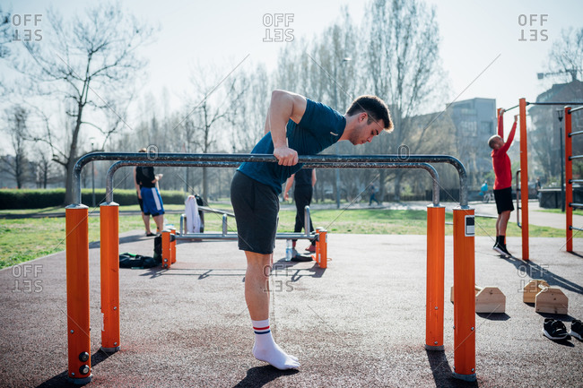 Calisthenics at outdoor gym, young man preparing to use parallel bars, full length