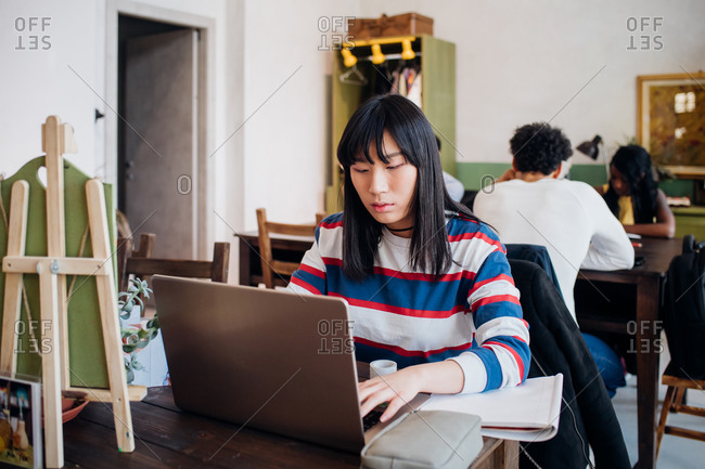 Young businesswoman remote working on laptop at cafe table