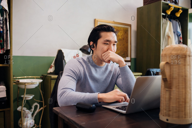 Young businessman remote working on laptop at cafe table
