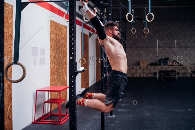 Bare chested young man training, swinging on exercise bar in gym
