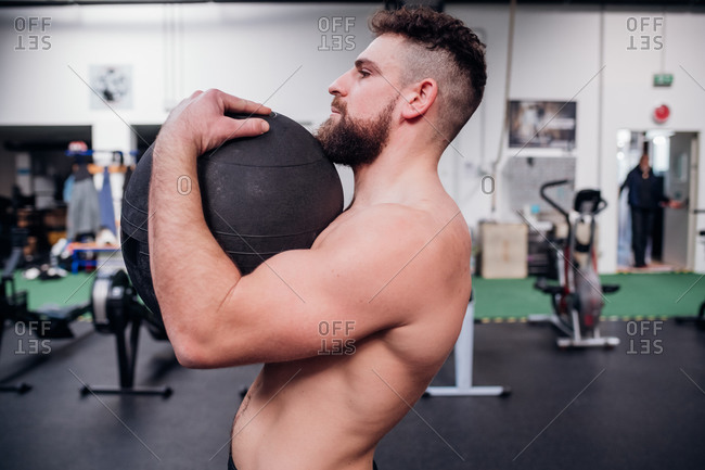 Young man training, lifting atlas ball in gym, side view