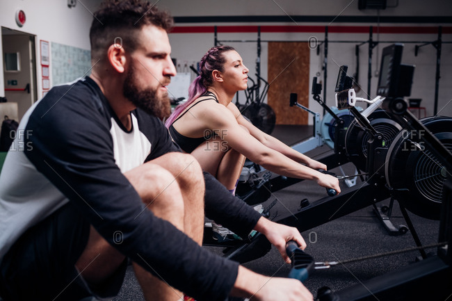 Young woman and man training on rowing machines together in gym, side view