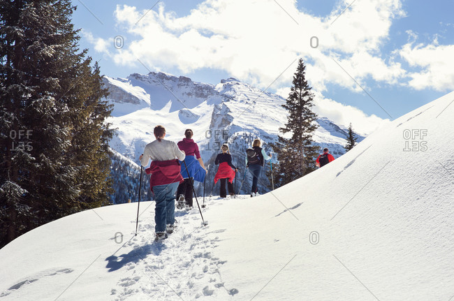 Mature couple and daughters snowshoeing in snow covered mountain landscape, rear view, Styria, Tyrol, Austria