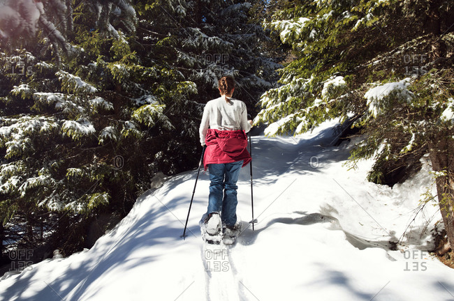 Teenage girl snowshoeing in snow covered mountain forest, rear view, Styria, Tyrol, Austria