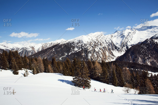 Mature couple and daughters snowshoeing in snow covered mountain landscape, distant view, Styria, Tyrol, Austria