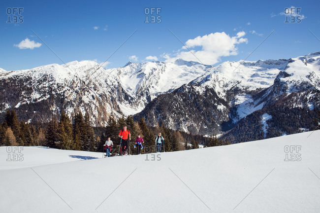 Mature couple and daughters snowshoeing in snow covered mountain landscape, Styria, Tyrol, Austria