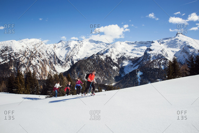 Mature couple and daughters snowshoeing uphill in snow covered mountain landscape, Styria, Tyrol, Austria