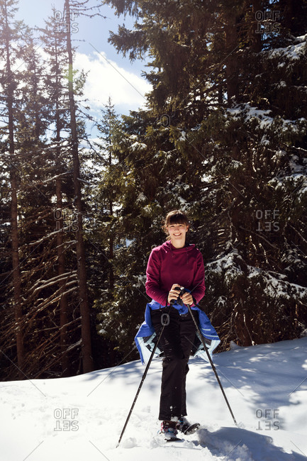 Teenage girl snowshoeing in snow covered mountain forest, portrait, Styria, Tyrol, Austria