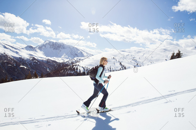 Mature woman snowshoeing up snow covered mountainside, Styria, Tyrol, Austria