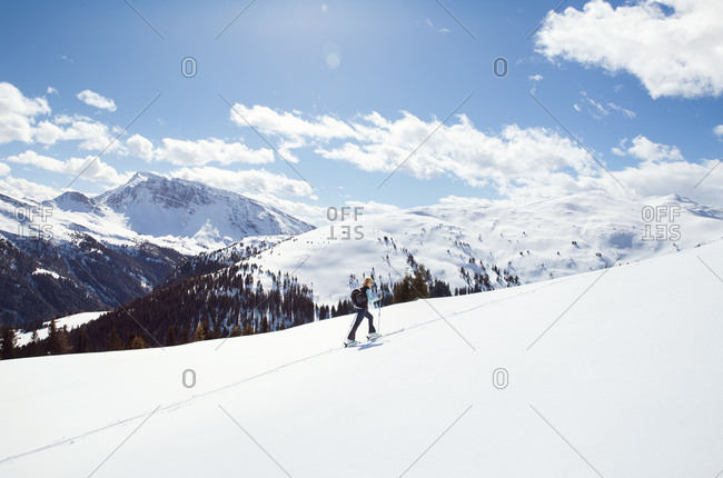 Mature woman snowshoeing up snow covered mountainside, distant view, Styria, Tyrol, Austria