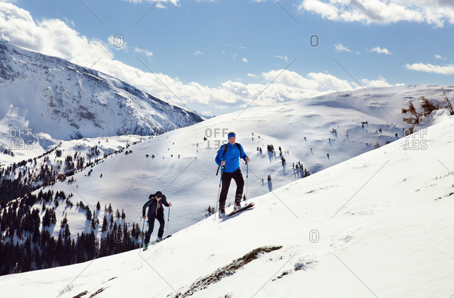 Mature skiing couple moving up snow covered mountain,  Styria, Tyrol, Austria