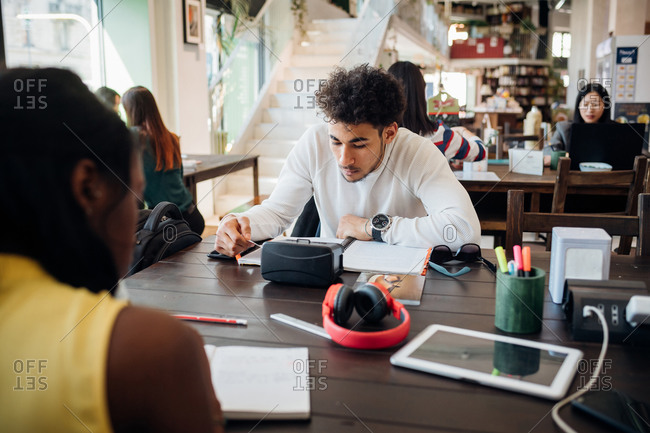 Young businessman and woman remote working at cafe table