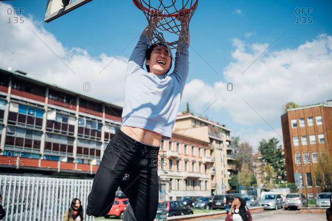 Young man hanging from basketball hoop at city basketball court