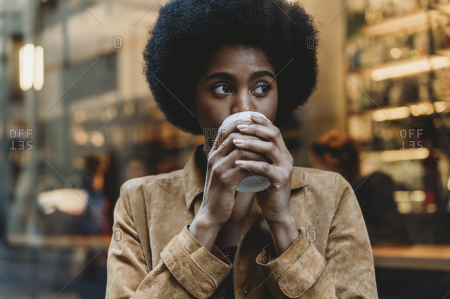 Young woman with afro hair having hot drink in front of cafe