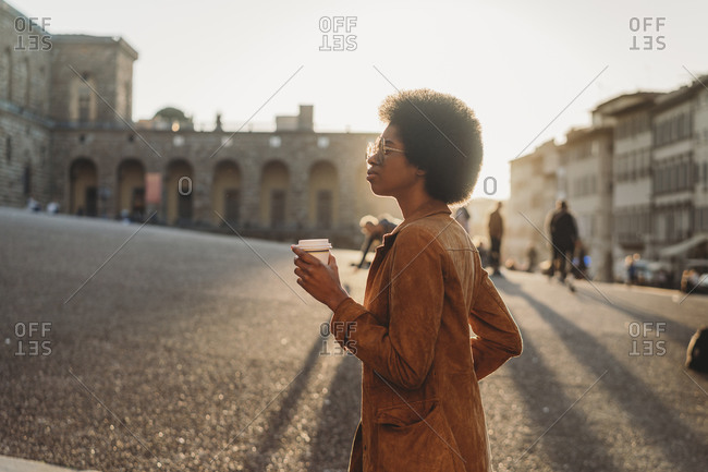 Young woman with afro hair exploring city, Florence, Toscana, Italy