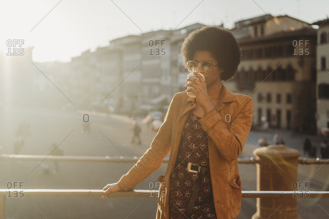 Young woman with afro hair having hot drink in city, Florence, Toscana, Italy