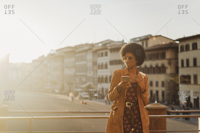 Young woman with afro hair having hot drink, using smartphone in city, Florence, Toscana, Italy