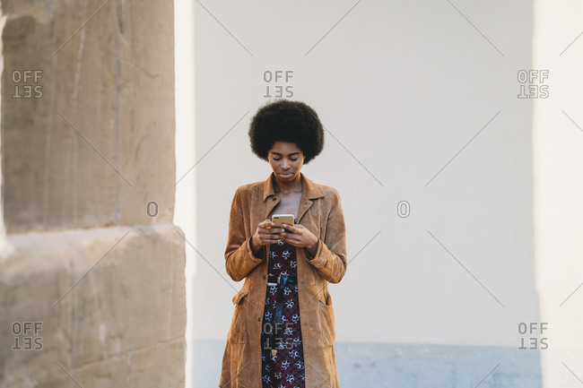 Young woman with afro hair using smartphone in corridor