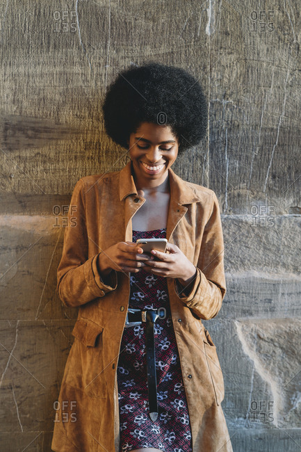 Young woman with afro hair using smartphone, leaning against stone wall