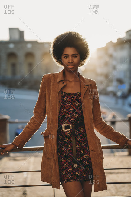 Young woman with afro hair leaning against handrail, Florence, Toscana, Italy