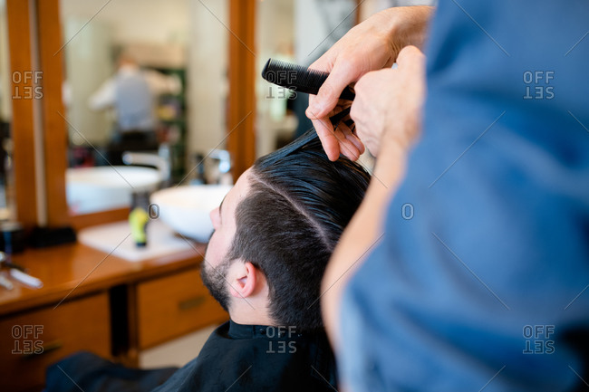 Hairdresser combing customer's hair in barber shop
