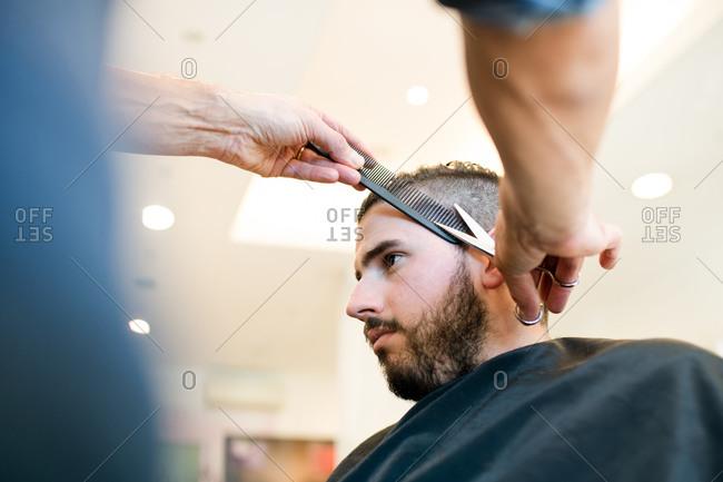 Hairdresser trimming customer's hair in barber shop