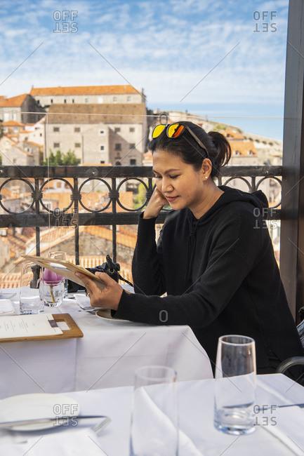 Woman looking at the menu at a rooftop restaurant in Dubrovnik, Dubrovacko-Neretvanska, Croatia