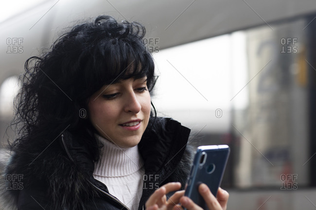 Mid adult woman using smartphone touchscreen in city