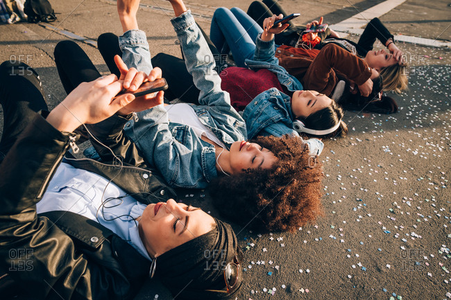 Friends together on curb taking selfie and using smartphones, Milan, Italy