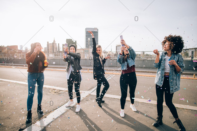 Friends celebrating with confetti and soap bubbles in street, Milan, Italy