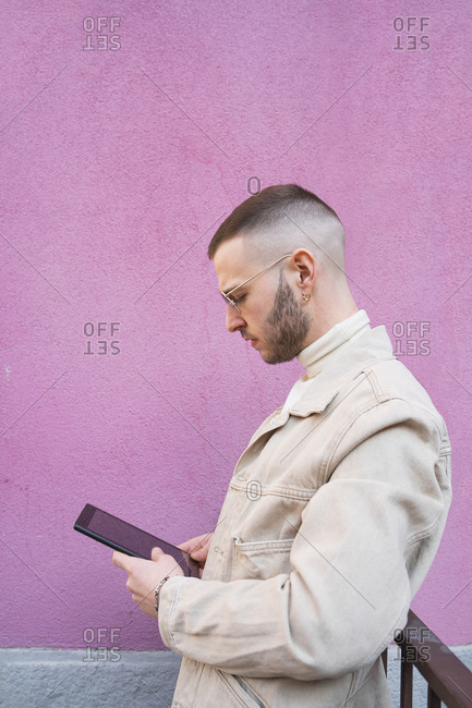 Young man using digital tablet, pink background