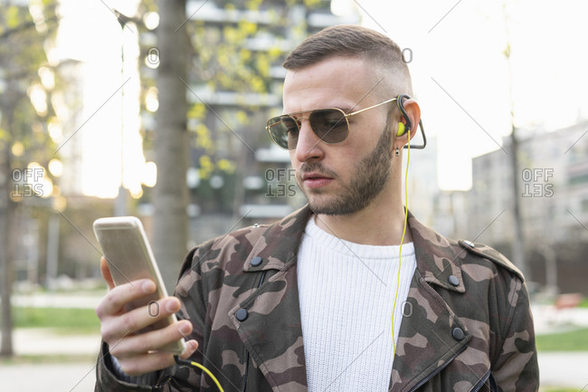 Young man using smartphone in city, Milano, Lombardia, Italy