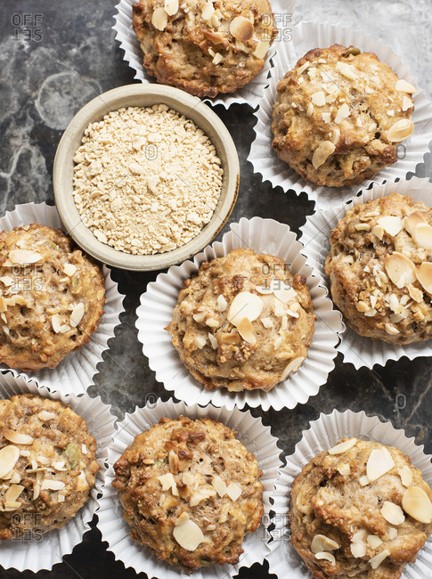 Still life of whole meal muffins in cake cases with bowl of oats, overhead view
