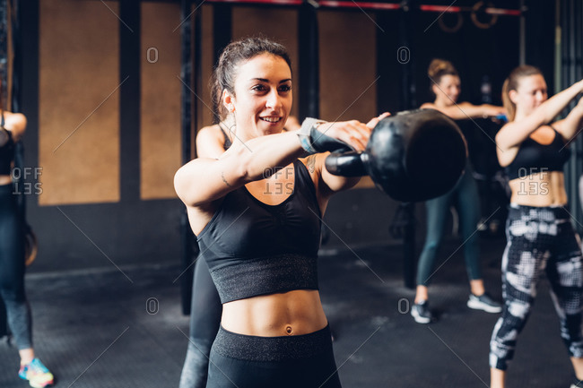 Women training in gym, lifting kettle bells