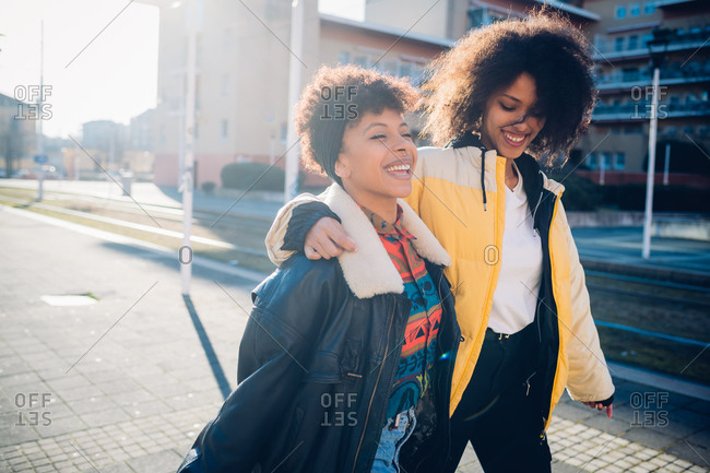 Two cool young female friends strolling on sunlit urban sidewalk
