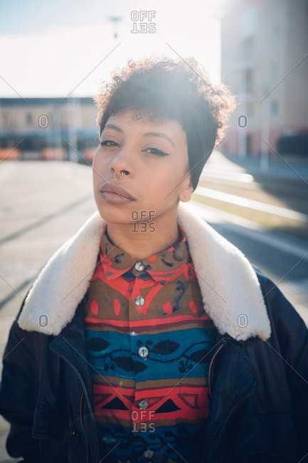 Cool young woman with nose piercing on sunlit urban sidewalk, portrait