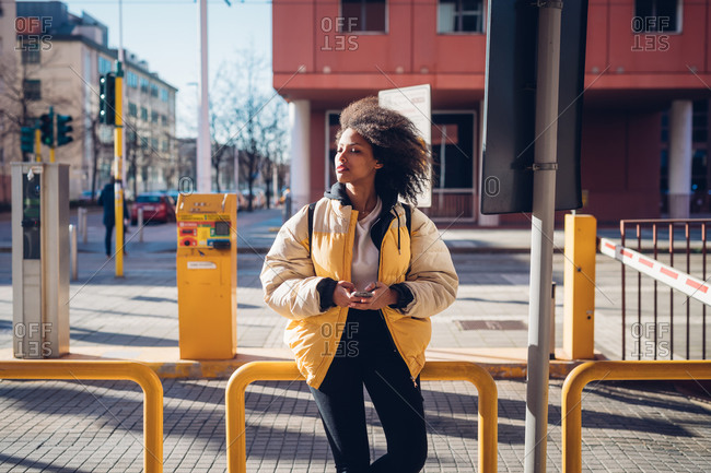 Cool young woman waiting at city tram station