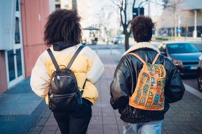 Two young women carrying backpacks strolling on urban sidewalk, rear view