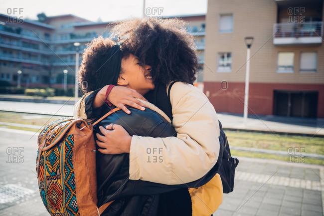 Two young women hugging on urban sidewalk