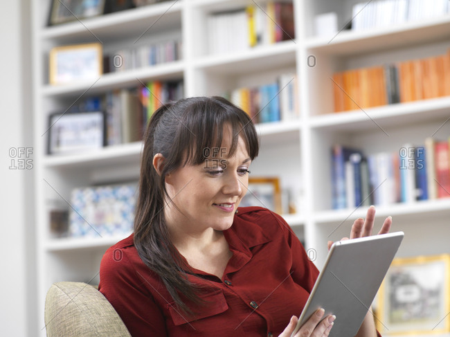 Woman relaxing at home on her digital tablet which she uses for social media, email and internet shopping