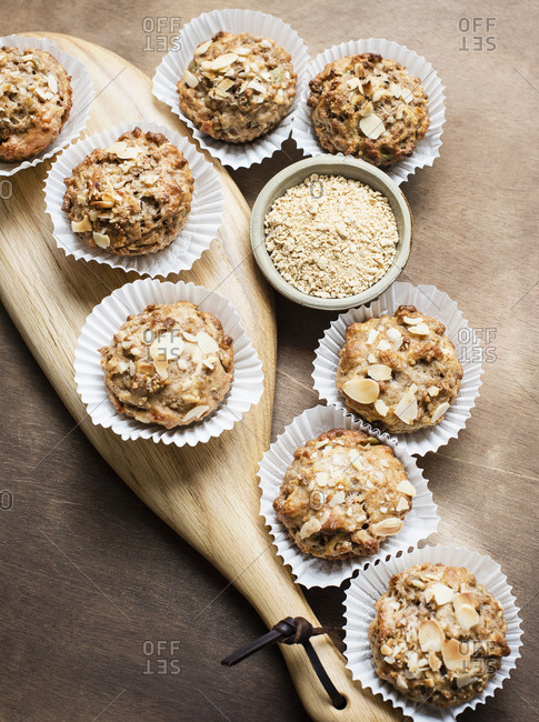 Still life of whole meal muffins on cutting board with bowl of oats, overhead view