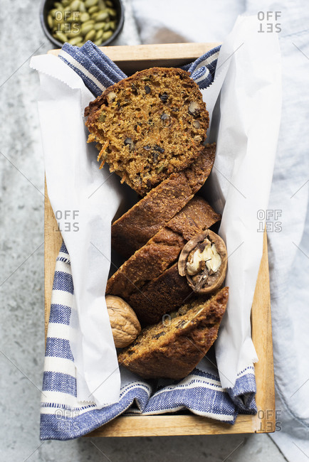 Still life of walnut and pumpkin seed cake sliced and  wrapped in tea towel in wooden box, overhead view